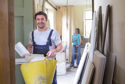 A young couple smile at the camera while working together on building a new home.