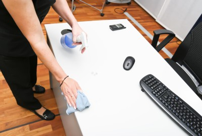 Charwoman cleaning a desk from stains with duster and cleanser spray, desk with computer keyboard, mouse and telephone.